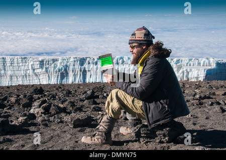 A trekker reading the Hemingway novel on the summit of Kilimanjaro with a glacier in background - Stock Photo