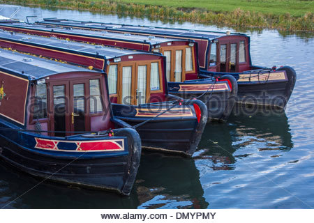 Four narrowboats tied up for the winter on the River Great Ouse at Ely, Cambridgeshire - Stock Photo