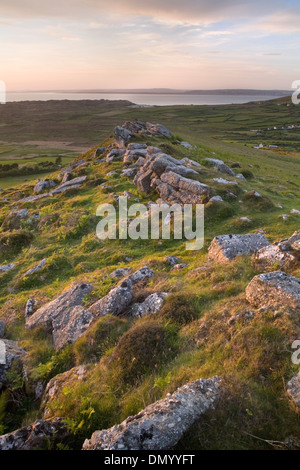 Boulders on the ridge of Rhossili Down near Llangennith, Gower Peninsula, overlook Rhossili Bay at sunset. - Stock Photo
