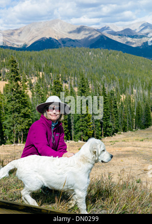 Woman and Platinum colored Golden Retriever dog hiking at Monarch Mountain, Colorado, USA - Stock Photo
