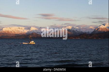 Small commercial fishing trawler heading out to sea in evening light in Homer Alaska. - Stock Photo