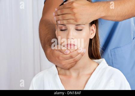 Masseuse Giving Head Massage To Woman - Stock Photo