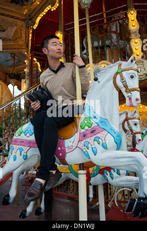 Paris, France, Young Chinese Man, on French Merry-go-Round, Mange, - Stock Photo