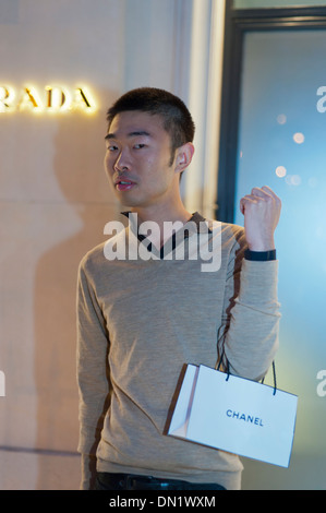 Paris, France, Portrait Young Chinese Tourist, Holding Chanel Bag, Shopping at Night, Avenue Montaigne, Prada Store - Stock Photo