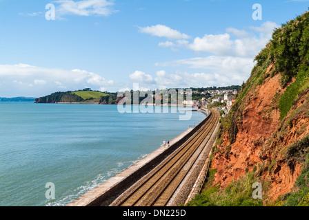 View along the railway line that runs along the Devon coast towards Dawlish on a sunny summer day - Stock Photo