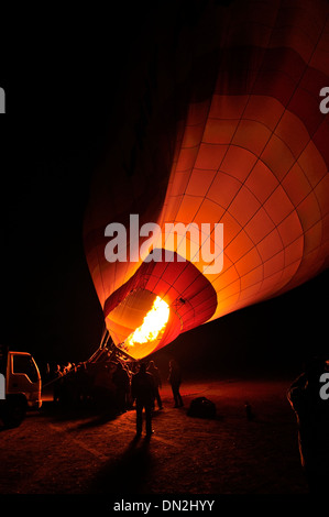 Inflating hot air balloon prior to early morning ascent over west bank of Luxor, Upper Egypt - Stock Photo