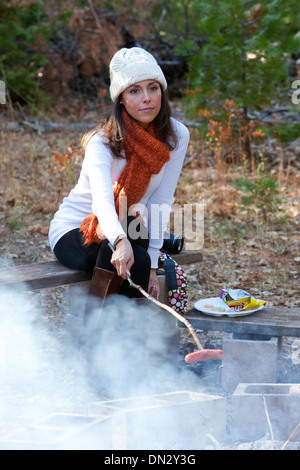 Woman roasting a Hot Dog over a smoky fire - Stock Photo