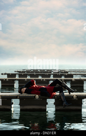 a woman in a red coat is lying on a jetty - Stock Photo