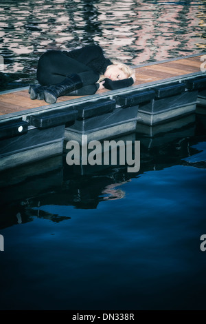 a woman in black clothes is lying on a jetty - Stock Photo