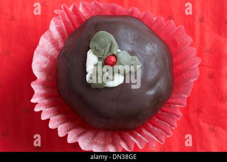 Christmas pudding chocolate truffle cake on red background - Stock Photo