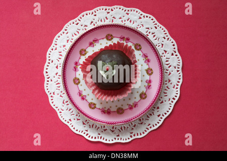 Christmas pudding chocolate truffle cake on pink decorative plate and doilie - Stock Photo