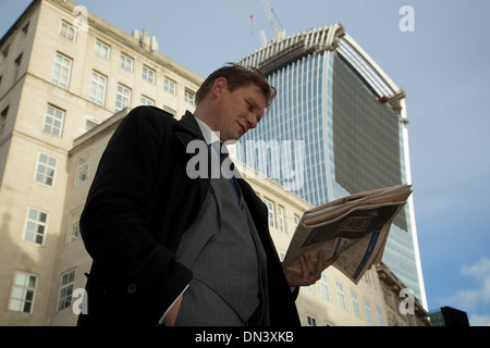 A City of London businessman reads the Financial Times with the 'Walkie Talkie' building in the background - Stock Photo