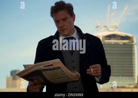A City of London businessman looking worried as he reads the Financial Times with the 'Walkie Talkie' building in - Stock Photo