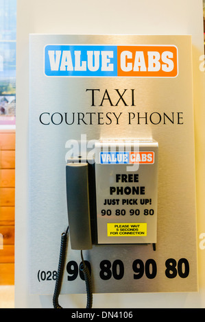 A courtesy phone for Value Cabs taxi company in Belfast in a local hotel - Stock Photo