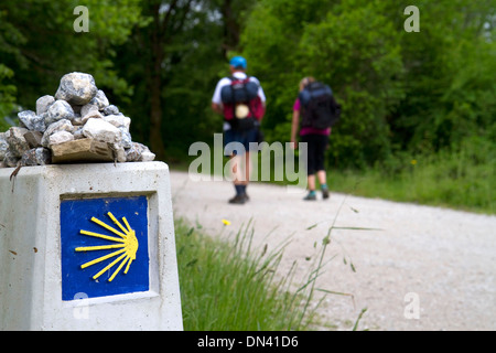 Pilgrims walk near a marker along the Camino De Santiago, the Way of St. James pilgrimage route, Navarra, Spain. - Stock Photo