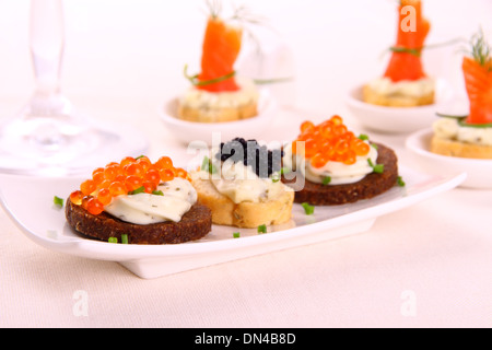 Red and black caviar on bread chunks as snack, close up - Stock Photo