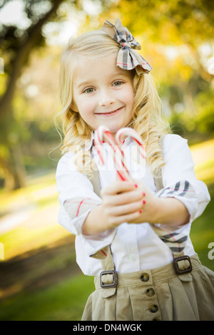 Cute Little Girl with a Bow in Her Hair Holding Her Christmas Candy Canes Outdoors. - Stock Photo