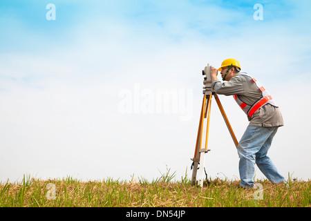 Surveyor engineer making measure on the field - Stock Photo