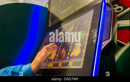Man playing fixed odds gaming machine in Bookmakers in England. UK - Stock Photo