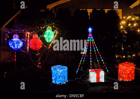 Christmas lighting display with wrapped gifts and tree decorations on the front lawn of a house - Stock Photo