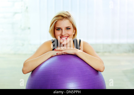 Young cheerful fit woman leaning on the fitball - Stock Photo