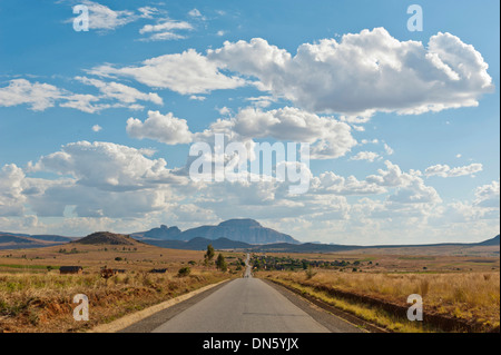 Long straight road, vast arid landscape, sky with clouds, Isalo National Park near Ranohira, Madagascar - Stock Photo