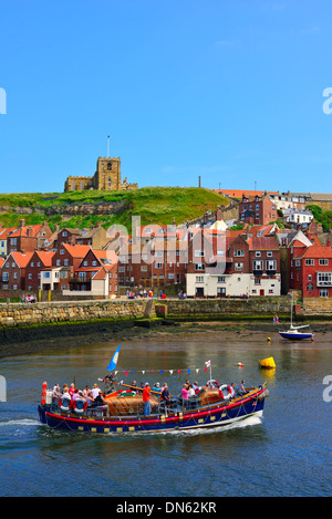 Excursion boat on the River Esk, St. Mary's Church at back, Whitby, North Yorkshire, England, United Kingdom