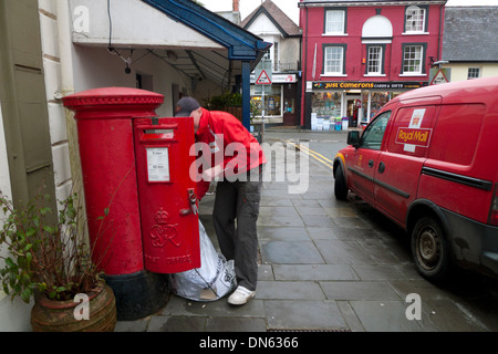 A postal worker emptying mail into a sack from a red postal box next to a Post Office van Llandovery Wales UK   - Stock Photo