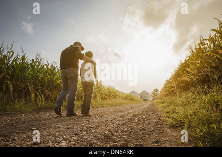 Caucasian father and son walking on dirt road through farm - Stock Photo