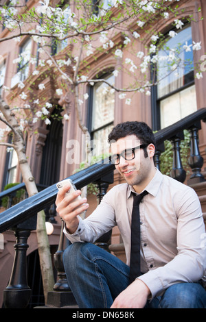 Hispanic businessman using cell phone on front steps - Stock Photo