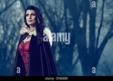 Woman outside among trees in the fog wearing a dark cape - Stock Photo