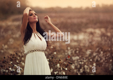 Woman in white dress standing in cotton field - Stock Photo
