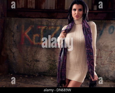 Fashion portrait of woman standing in abandoned warehouse - Stock Photo