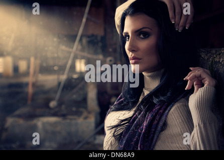 Fashion portrait of woman in abandoned warehouse with light beam - Stock Photo