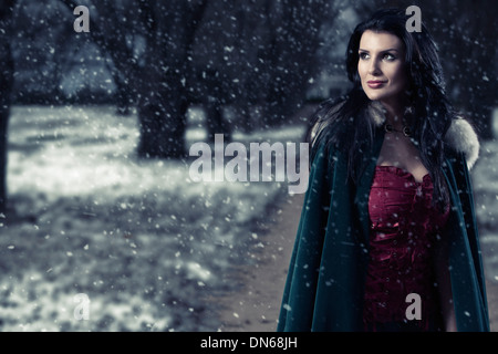 Woman in green cape walking down snowy path looking thoughtful and happy - Stock Photo