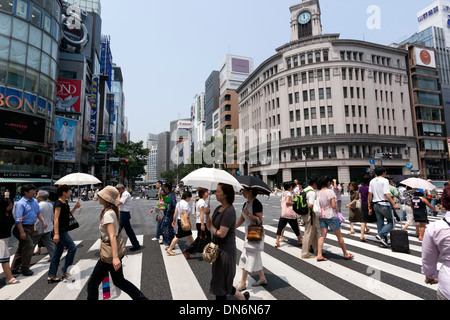 Multitude of people walking through a pedestrian crossing in Ginza . Tokyo. - Stock Photo