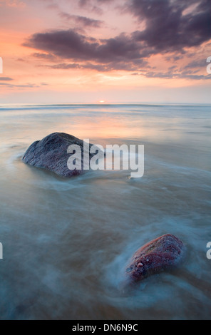 Rocks prutruding through the sea at high tide at Rhossili Bay, Gower, Wales while the sun sets over the horizon - Stock Photo