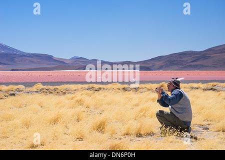 Bolivian man looking at yellow grasses lining the shore of Laguna Colorada (red lagoon), Reserva de Fauna Andina Eduardo Avarda,