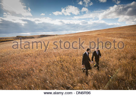 Businessmen walking through field - Stock Photo