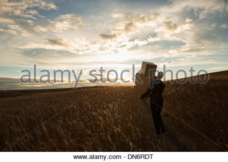 Businesswoman with stacked boxes walking through field at dusk - Stock Photo