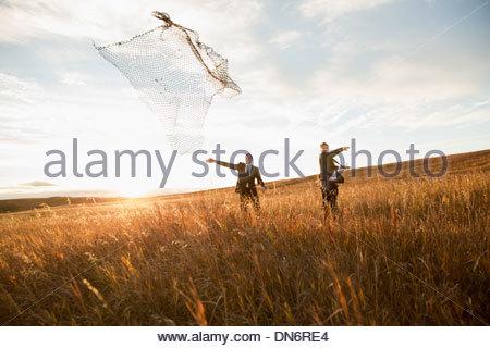 Businessmen throwing fishing net on field - Stock Photo