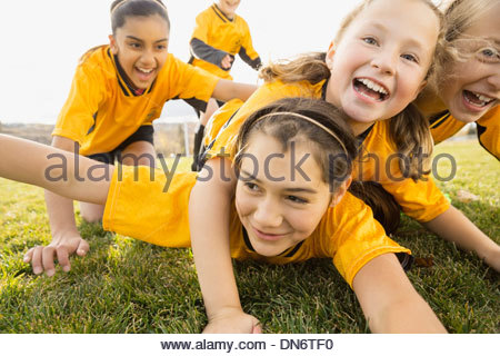 Soccer players celebrating success on field - Stock Photo