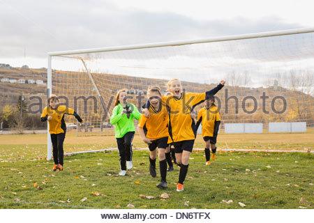 Girls soccer team celebrating goal on field - Stock Photo