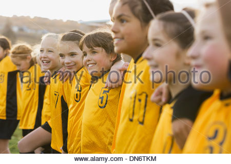 Soccer team smiling on field - Stock Photo
