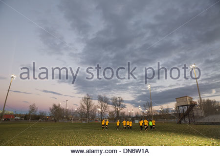 Girls soccer team on field at dusk - Stock Photo