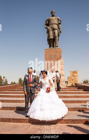 Bride and groom in front of Statue of Amir Timur, also known as Temur and Tamerlane, Shakhrisabz, Uzbekistan - Stock Photo