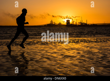 Man jogging on North Gare beach near Seaton Carew, north east England. Redcar Steelworks in distance. - Stock Photo