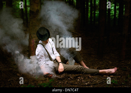 Man surrounded by smoke with gun in hand leaning on tree - Stock Photo