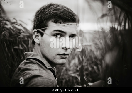 Young man standing in cornfield, portrait - Stock Photo
