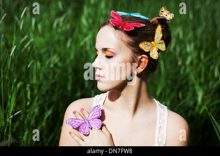 Young woman with closed eyes and artificial butterflies - Stock Photo